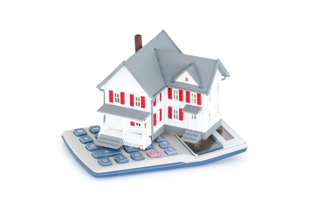 Miniature house with a calculator against a white background